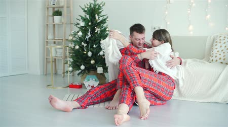 télen : Loving Couple in Red Pajamas Covering with a Plaid and Sitting near Christmas Tree. They Hugging and Kissing and Enjoying Time Together. Winter Holiday Celebration and People Concept