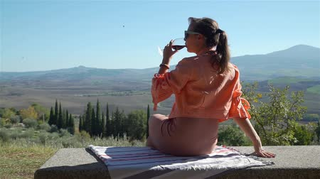 tasting : Young Woman Drinking Red Wine and Enjoying Beautiful Tuscan Landscape while Sitting on the Viewpoint. Agritourism, Ecotourism and Local Organic Production Concept Stock Footage