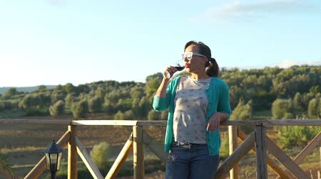 tasting : Young Beautiful Woman in Sunglases Having a Glass of Local Red Wine at Sunset. Beautiful Italian Countryside Landscape is on the Background. Agritourism, Ecotourism