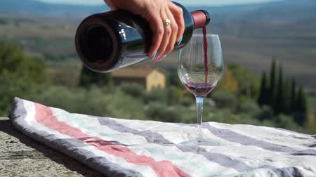 Close Up of Woman Pouring Red Wine into a Glass. Tasting Local Freshly Made Wine in Tuscany, Italy. Agritourism, Ecotourism and Local Organic Production Concept