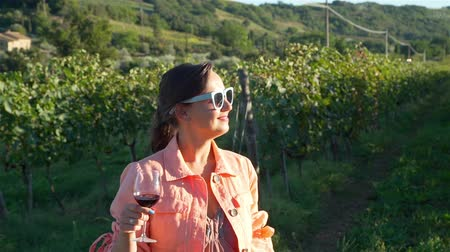 Young Woman in Sunglasses Enjoying View of Tuscan Vineyards at Sunset. Female Tourist Travel Visiting Vineyard Site nad Tasting Local Wine. Tuscany, Italy. Slow Motion. Agritourism, Ecotourism