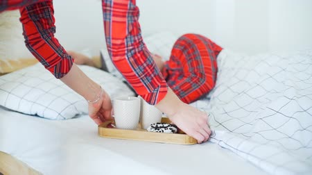 Good Morning! Young Girl Brings Breakfast to her Husband in the Bed. Hot Tea and Fresh Donuts in the Morning. Lifestyle, Romantic Relationships and People Concept