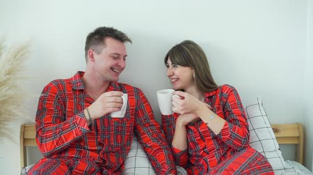 Young Smiling Couple in Red Pajamas Drinking Tea in Bed in the Morning. Man and Woman Laughing and Talking while Having Breakfast in Bed. Slow Motion. Lifestyle, Romantic Relationships Wideo