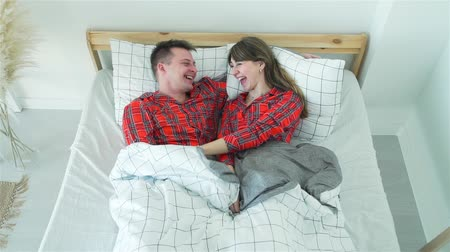 Young Man and Woman Fooling Around in their Bed in the Morning. Couple in Love Enjoing Time Together. The Concept of Family Happiness and Romantic Relationship