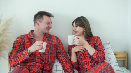 Young Smiling Couple in Red Pajamas Drinking Tea in Bed in the Morning. Man and Woman Laughing and Talking while Having Breakfast in Bed. The Concept of Family Happiness and Romantic Relationship