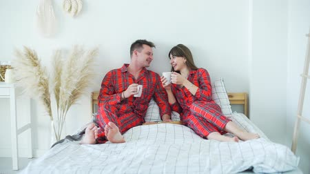 Young Married Couple Having Breakfast in Bed. Man and Woman Drinking Tea and Talking while Sitting in Bed. Slow Motion. Lifestyle, Romantic Relationships and People Concept