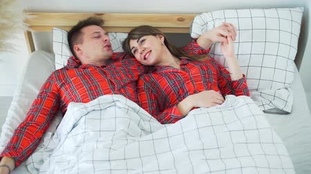 Young Loving Couple Lying and Talking in Bed in the Morning. Lifestyle, Romantic Relationships and People Concept