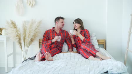 Young Married Couple Having Breakfast in Bed. Man and Woman Drinking Tea and Talking while Sitting in Bed. The Concept of Family Happiness and Romantic Relationship
