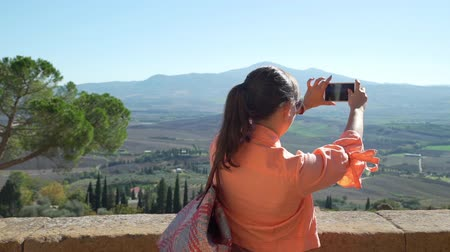 Female Tourist Taking Photos of Amazing Tuscan Landscape in Sunny Weather. Vacation in Italy. Concept of Holidays and World Travel Concept