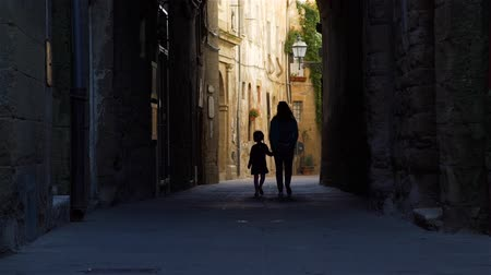 Silhouettes of Little Girl and her Mother Walking on Street of Pitigliano (Town and Commune in the province of Grosseto, Tuscany, Italy). Concept of Holidays and World Travel Concept