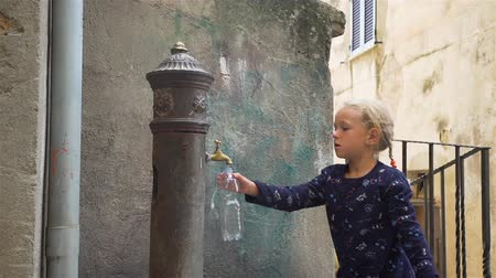 типичный : Cute Little Girl Filling Bottle with Fresh Water from Vintage Water Fountain on Italy Street. This Fountains are Popular in Some Italian Cities and People Called them Nasoni. Concept of Holidays