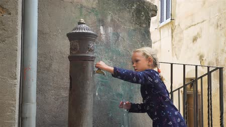 Little Girl Filling Bottle with Fresh Water from Vintage Water Fountain on Italy Street. This Fountains are Popular in Some Italian Cities and People Called them Nasoni. Slow Motion Stockvideo