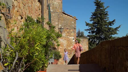 Young Mother and her Cute Little Daughter Walking on Street of Pienza (Ancient Town and Commune in the province of Siena, Tuscany, Italy). Slow Motion. Concept of Holidays and World Travel Concept Stockvideo