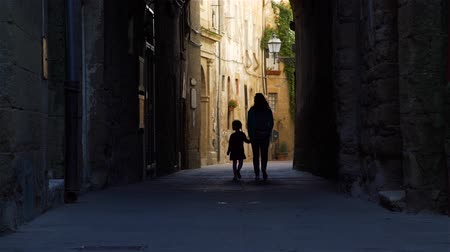 Silhouettes of Little Girl and her Mother Walking on Street of Pitigliano (Town and Commune in the province of Grosseto, Tuscany, Italy). Slow Motion. Concept of Holidays and World Travel Concept 動画素材