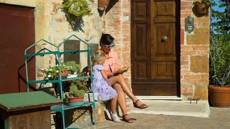 Young Mother and her Daughter Reading Book on an Ancient City of Italy in Sunny Day. Family, Leisure, Vacation and People Concept Stockvideo