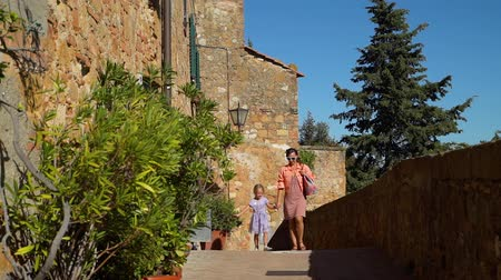 Young Mother and her Cute Little Daughter Walking on Street of Pienza (Ancient Town and Commune in the province of Siena, Tuscany, Italy). Concept of Holidays and World Travel Concept