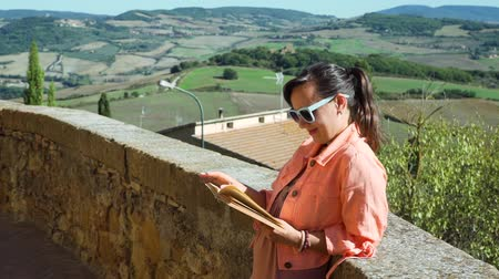 Young Woman Tourist Reading Book while Standing on the Ancient Street of Pienza in Tuscany, Italy. Beautiful Landscape of Tuscan Meadows and Hills is on the Background.