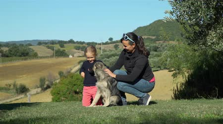 Little Girl with her Mother Petting the Dog while Sitting on the Grass. Beautiful Tuscan Landscape is on the Background. Pets and Animals Concept