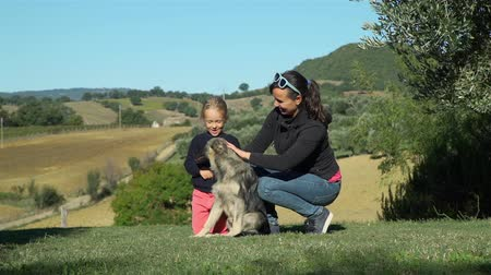 Little Girl with her Mother Petting the Dog while Sitting on the Grass. Beautiful Tuscan Landscape is on the Background. Slow Motion. Pets and Animals Concept