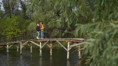Yound Family Enjoying View from Wooden Bridge over the Lake in Autumn Day. Harmony with Nature, Leisure and People Concept Stockvideo