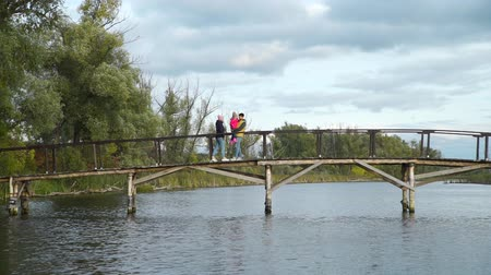 Young Family Walking Along a Wooden Bridge by a Lake in Slow Motion. Holiday in Nature. Harmony with Nature, Leisure and People Concept