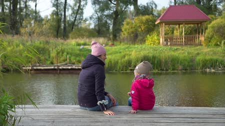 Little Girl and her Mother Talking while Sitting on a Pier near the Beautiful Lake in Autumn Day. Harmony with Nature, Leisure and People Concept 動画素材