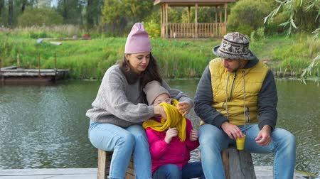 Young Family Having a Picnic near the Lake. Mother Helping her Daughter to Put a Warm Scarf. Family, Leisure and People Concept