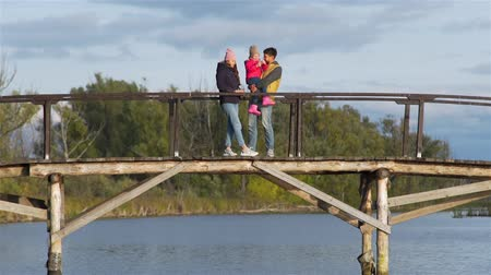 Young Man with his Daughter and Wife Enjoying Sunset while Standing on the Wooden Bridge over the Lake. Harmony with Nature, Leisure and People Concept 動画素材