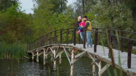 Young Family Standing on Wooden Bridge by a Lake. Thay Talking and Enjoying Time Together. Harmony with Nature, Leisure and People Concept Dostupné videozáznamy