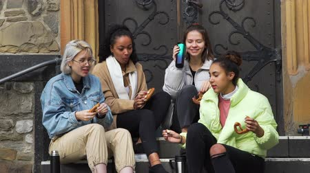 Multiracial Group of Girlfriends Eating Pretzels and Brushing Off Bee. Female Teens Spending Leisure Time Together while Sitting on the Steps of Ancient European Building. Friendship, Lifestyle Filmati Stock