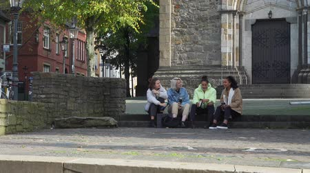 Mixed Race Young Girlfriends Drinking Coffee or Tea on the Steps in the Centre of an Old German City. They Talking and Smiling. People, Leisure, Friendship and Communication concept