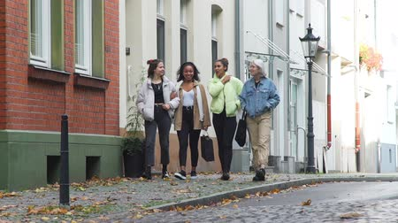 Four Mixed Race Teen Girlfriends Walking Near Bicycle Lane in the Centre of an Old German City in Autumn Day. People, Leisure, Friendship and Communication concept