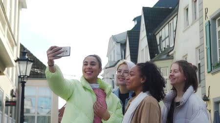 Smiling Multiethnic Young Girlfriends Taking Selfie by Camera of Smartphone on a German Street. Female Friends are Fooling Around Outdoors. Friendship, Lifestyle and People Concept