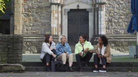 Four Multiracial Female Friends Talking while Sitting on the Steps in the Centre of an Old German City. They Holding Thermo Mug with Hot Tea or Coffee in their Hands.