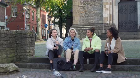 Four Multiracial Female Teens Talking while Sitting on the Steps in the Centre of an Old German City. They Holding Thermo Mug with Hot Tea or Coffee in their Hands in Autumn Day.