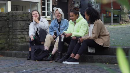 Young Female Friends Having Good Time Outdoors. Multiracial Group of Teens Talking and Drinking Tea or Coffee while Sitting on the Steps in the Centre of an Old German City.