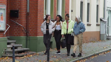 quatro : Ratingen, Germany - October 21, 2019: Four Mixed Race Teen Girlfriends Walking Near Bicycle Lane in the Centre of an Old German City in Autumn Day.
