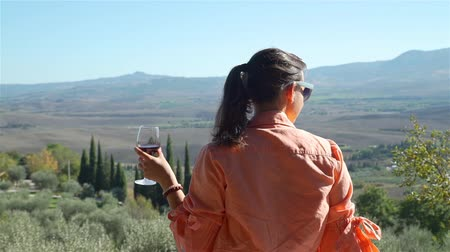 winemaking : Beautiful Young Woman Drinking Red Wine and Enjoying Amazing View of Val d Orcia, Region of Tuscany, Central Italy. Vacation, Holidays and World Travel Concept