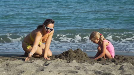 Young Mother Playing with her Daughter on the Sand Beach. They Building Sand Castle. Slow Motion. Concept of Family Holidays and Vacation