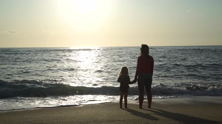 Silhouettes of Little Girl and her Mother at Sunset. They Standing on the Sand Beach and Enjoying the View. Slow Motion. Concept of Tourism, Leisure at Sea, Travel in Summer Time