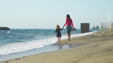 Back View of Young Woman and her Little Daughter Walking Barefoot Along Seashore at Sunset. Slow Motion. Concept of Family Holidays, Vacation and Travel in Summer Time Filmati Stock