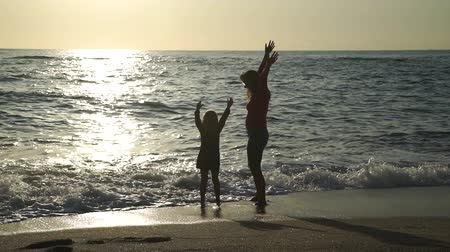 Silhouettes of Woman with Little Daughter Having Fun on Beach at Sunset. They Standing in the Water and Rising their Arms Up. Concept of Family Holidays and Vacation in Summer