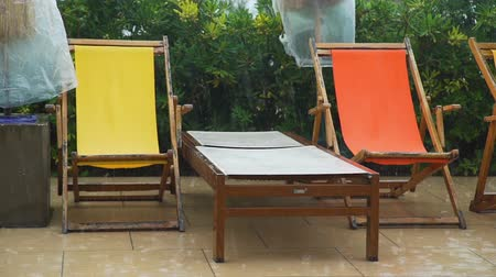 deck chairs : Comfortable Sunbed and Colorful Deck Chairs on Rainy Day. Rain Time at The End of Tourist Season. Vacation with Bad Weather Concept