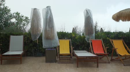 サンベッド : Empty Deck Chairs and Closed Parasols in Rainy Day on Tropical Resort. The End of Tourist Season. Vacation with Bad Weather Concept