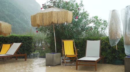 deck chairs : Stormy Weather on Tropical Resort. Wet Deck Chairs and Closed Parasols in the Rain Time. The End of Tourist Season. Vacation with Bad Weather Concept Stock Footage