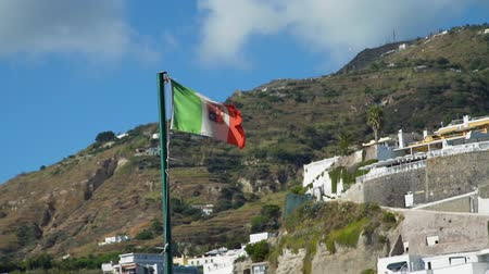Italian Flag with National Emblem Fluttering in the Wind. Beautiful Town of Sant Angelo on Ischia Island is on the Background. Concept of Holidays, Vacations and World Travel Concept