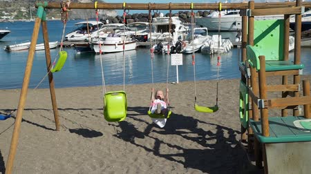 Little Girl Swinging on the Beach near Yachts and Harbor. Beautiful Playground in Sant Angelo Village on Ischia Island, Italy. Concept of Holidays, Vacations and World Travel Concept