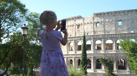gladiador : Cute Little Girl in Violet Dress Taking Photos of Coliseum or Colosseum with Smartphone in Rome. Slow Motion. Concept of Holidays, Vacations and Travel in Europe