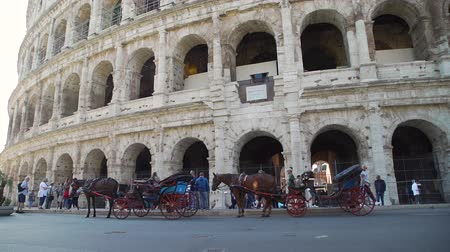 colosseo : Rome, Italy - October 5, 2019: Horse Carriages and Lots of Tourists near Colosseum (Coliseum) in Rome. Concept of Holidays, Vacations and Travel in Europe