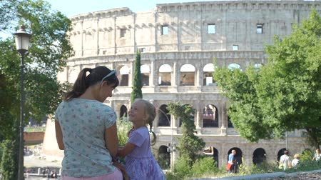 Smiling Little Girl with Mother Sitting and Talking over Colosseum (Coliseum) in Rome. Family Holidays, Vacation and People Concept